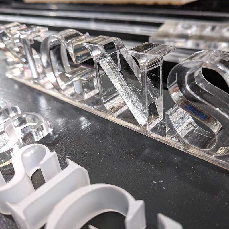 Laser cut clear acrylic lettering that says Signs