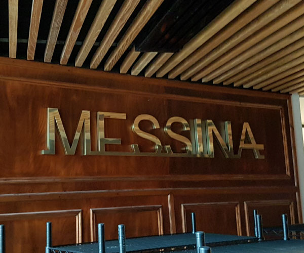"""Polished brass logo mounted onto a hamper. The sign reads """"Messina"""""""